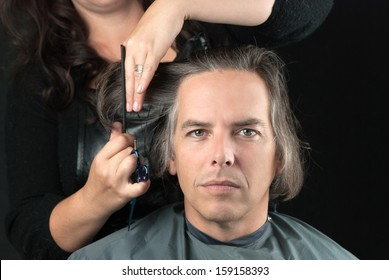 Close-up of a serious man looking to camera while his long hair is cut off for a cancer fundraiser.