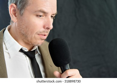 Close-up of serious man speaking into microphone, side.