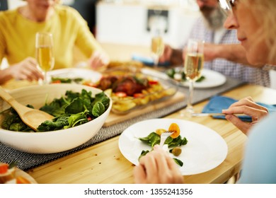 Close-up of serious mature lady sitting at dining table and eating fresh salad using fork and knife during dinner party with friends
