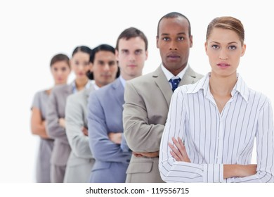 Close-up of serious people dressed in suits crossing their arms in a single line with focus on the first woman