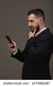 Closeup of a serious and worried businessman using cellphone against grey background.