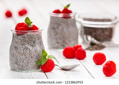 Closeup of served glass jars filled with sweet pudding of chia seeds and garnished with fresh raspberry and mint