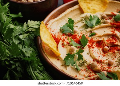 CLose-up of served hummus. Healthy hummus dip with vegetables on a wooden background. Middle eastern restaurant concept.