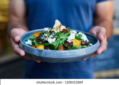 Closeup of a server standing outside of a bistro holding a plate with a delicious mixed salad of butternut, lettuce, olives and feta