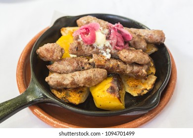 A closeup to a serving of Cevapi a typical dish in Serbia. Consisting of mixed meat sausage fingers, potatoes, cream cheese and bread.