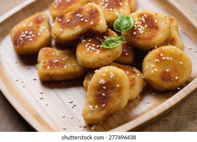 Close-up of sesame chicken nuggets on a bamboo tray, studio shot