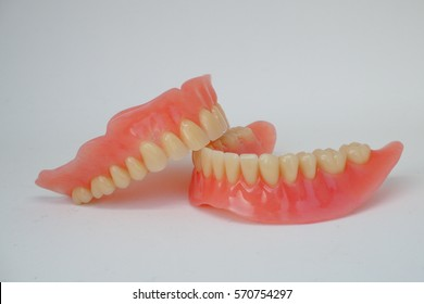 Close-up set of full denture; upper and lower removable denture with pink plastic gum,anterior and posterior artificial teeth on white background (isolated)