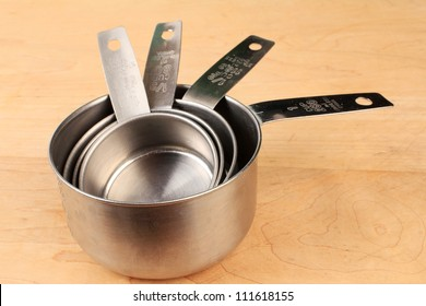Closeup of set of stainless steel measuring cups on wooden cutting board in domestic kitchen.