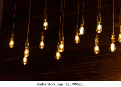 Close-up set of vintage glowing light bulbs hanging on black background. Decorative antique style light bulbs in restaurant