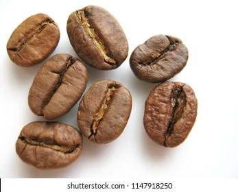 A closeup of seven coffee beans on the white background.