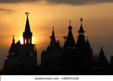 Close-up of several black silhouettes of the towers of the Izmailovo Kremlin against the sunset orange sky and a ray of sun