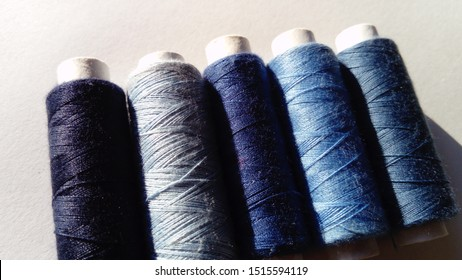 Close-up of several bobbins of thread in different shades of blue. Spools of thread located on a white background