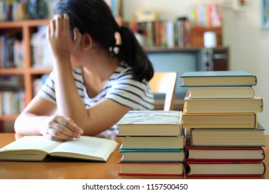 Close-up of several books stacked on a table in a library. The girl is reading a tired book as a background selective focus and shallow depth of field