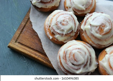 Closeup of several cinnamon buns.Beautiful fresh cinnamon rolls close-up on wooden grunge texture table. Fragrant homemade cakes, Cinnabon. A Cup of tea on a white saucer, cinnamon sticks.