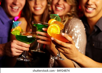 Close-up of several cocktails in young people hands