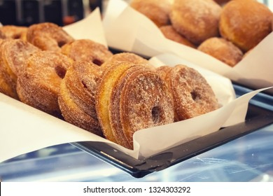 Closeup of several freshly baked warm Cronuts sitting in pans on a glass display at a French pastry shop