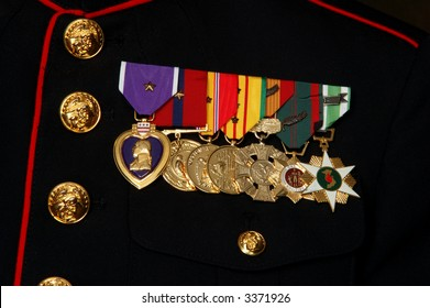 Close-up of several military medals including a Purple Heart on a dark blue dress Marine uniform