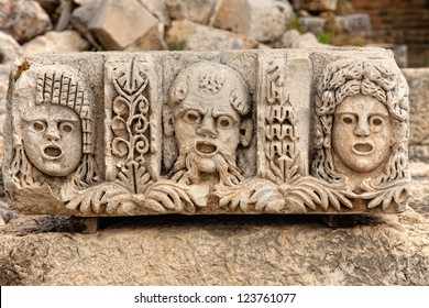 Closeup of several stone masks at an ancient theater in Myra Turkey