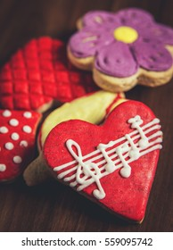 Close-up of several sugar cookies with royal icing glaze of different colors, one red heart-shaped with musical notes in foreground