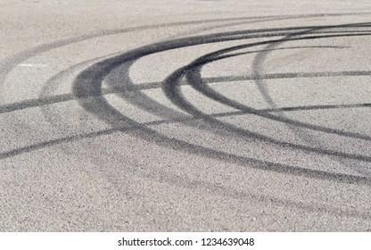 Close-up of several tire skid marks on asphalt
