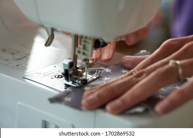 Close-up of a sewing machine on which a Corona face mask is sewn