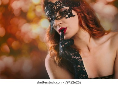 Closeup of sexy beatiful red haired woman with laced gloves and venetian mask in front of blur night lights. New year night and event party celebration. Luxury and glam lifestyle.