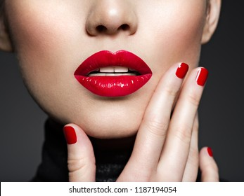 Closeup sexy female lips with red lipstick. Glamour fashion bright gloss make-up and manicure.