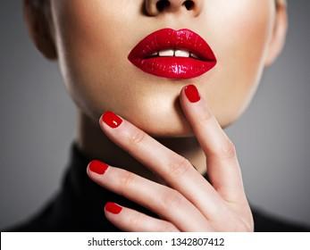 Closeup sexy female lips with red lipstick. Glamour fashion bright gloss make-up and manicure.
