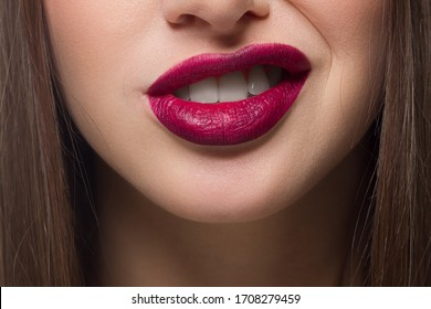 Close-up of sexy female lips with tongue. Clean skin and a clear lip contour are outlined with a fashionable marsala lipstick. White teeth and the beauty of smile for stamotologii, spa or cosmetology