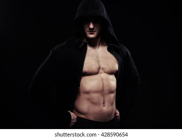 Close-up of sexy guy in dark sport jacket with hood over his head showing well trained muscular body, hands on hips