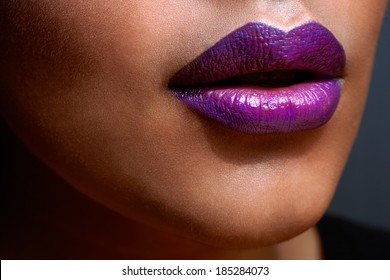 closeup of woman�¢??s sexy lips with purple ombre style lipstick on tanned skin