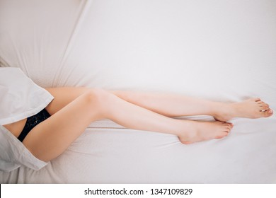 Closeup of sexy slender female legs on white bed. Woman wearing black panties and white shirt relaxing lazing in bedroom. Horizontal photo, top view. Beauty and skin care concept. Copy space.