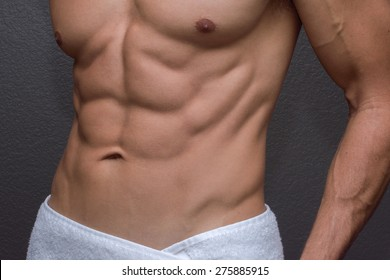 Closeup of sexy torso showing muscular lean abdominals and chest of tan Caucasian man with white towel wrapped around waist next to textured gray wall background