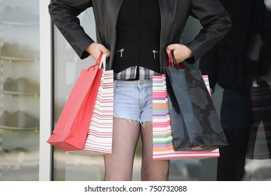 Close-up of sexy woman carrying shopping bags in front of shop window