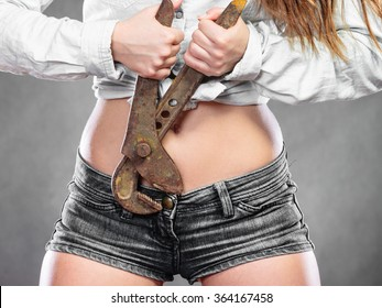 Closeup of sexy woman holding monkey wrench gas grips. Strong girl feminist working in man profession. Gender social issue.