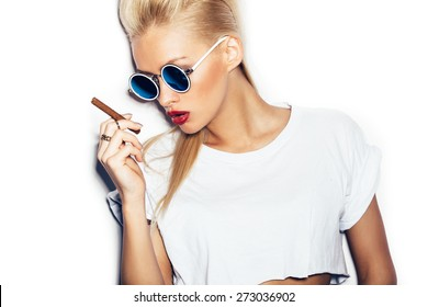 Close-up of sexy woman in sunglasses and white shirt smoking cigar.  White background, not isolated