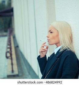Close-up of sexy woman in sunglasses and white shirt smoking cigar