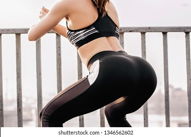 Closeup of sexy young sports girl in stylish sportswear squatting on bridge. Beautiful slim fitness woman doing workout, exercising outdoors. Athletic girl doing crossfit squats. Healthy lifestyle