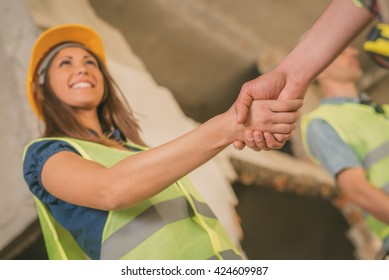 Close-up of a shaking hands of a construction workers in building damaged in the disaster. Selective focus.
