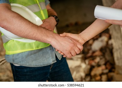 Close-up of a shaking hands of a construction workers in building damaged in the disaster.