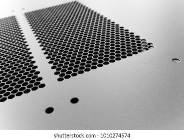 Close-up, shallow focus of a meshed style cooling panel used on a main frame computer, housed in a  data centre. The honeycomb holes aid active venting of hot air within the computer.
