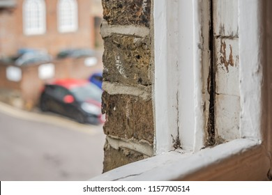 Close-up, shallow focus of a wooden styled, sash window seen in the opened position. Signs of rot can be seen on the wood. In the distance is part of a carpark used for this London office block.