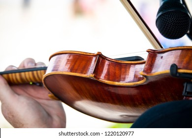 A closeup shallow focused shot from behind of the detailed side of a hand made maple violin being played by a young musician.