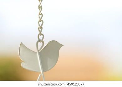 Close-up shape bird wind chime with hanging chains
