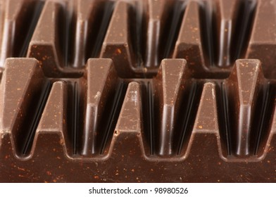 Close-up of shaped dark chocolate with crushed nuts.