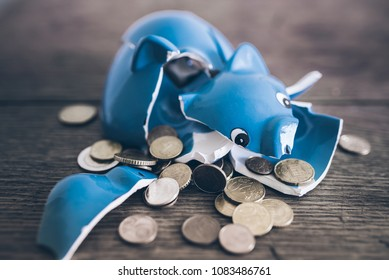 closeup of shattered broken piggy bank with coins on rustic wooden table