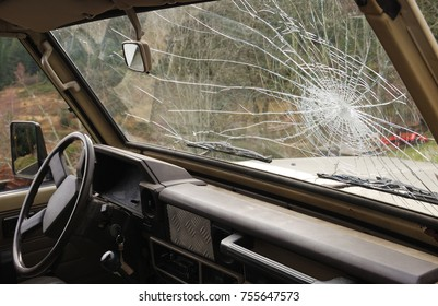 Close-up at shattered car windshield, country road in background