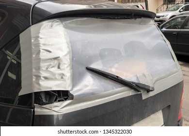 close-up of shattered rear window of the dirty car is covered with cellophane tape. Vandalized car passenger window temporarily covered with tape