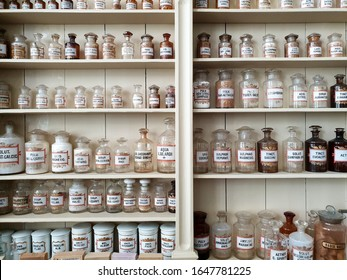 A close-up of the shelves in an old pharmacy, glass Latin labeled bottles filled with chemicals for making medicine.