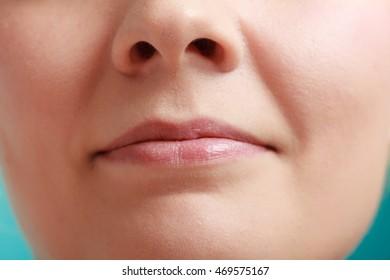Closeup shiny glossy female lips. Part of face.